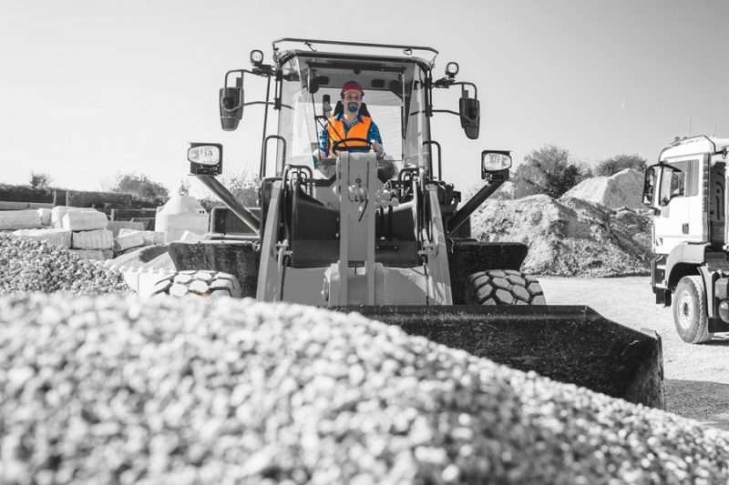 Construction workers moving aggregate wheel loader