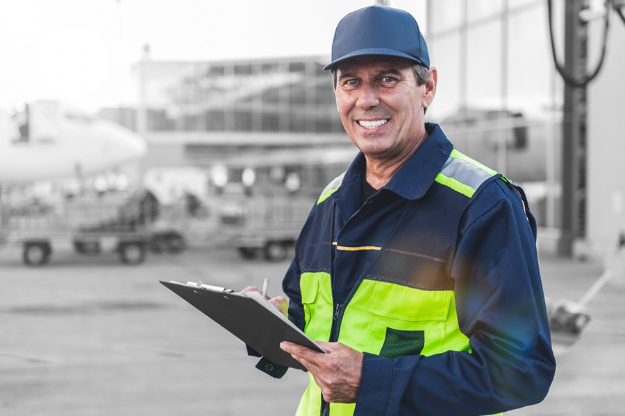 Airport worker in front of an airplane and some airport vehicles
