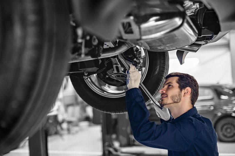 Auto mechanic examining car suspension