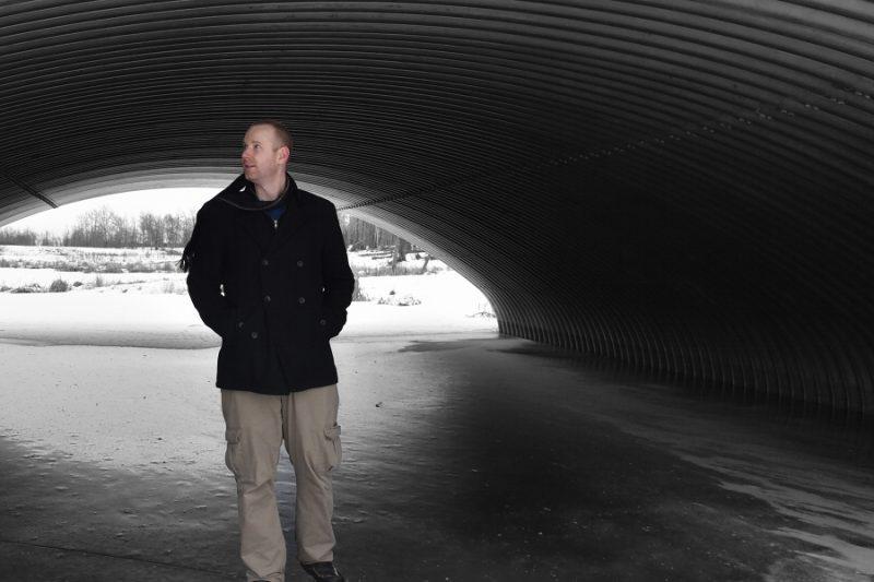 a man in a coat walks through a large culvert in winter