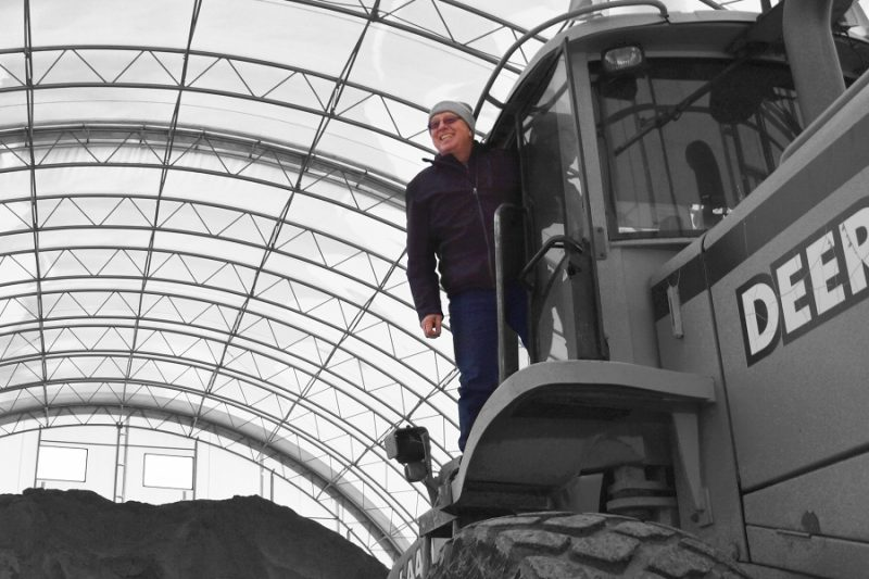 Worker stands atop construction equipment inside a fabric shelter
