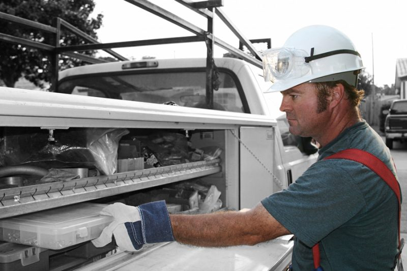 Worker accessing tools from an upfitted work truck