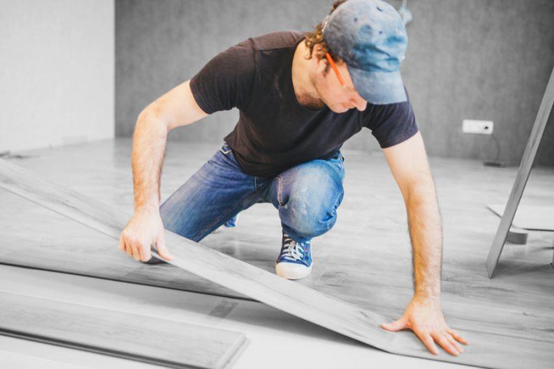 Worker installing commercial flooring
