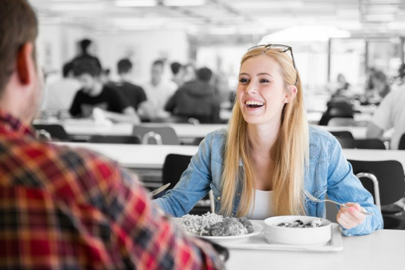 Two people enjoying eating in a cafeteria