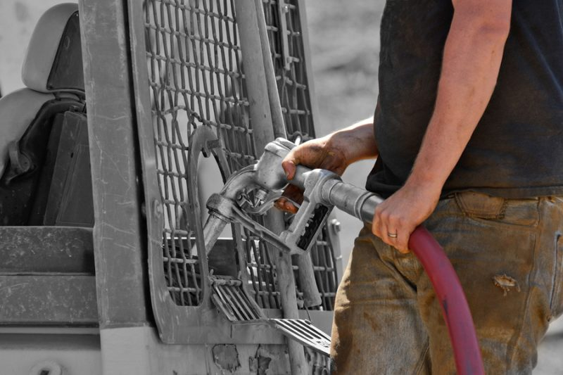 Worker refuels some construction equipment