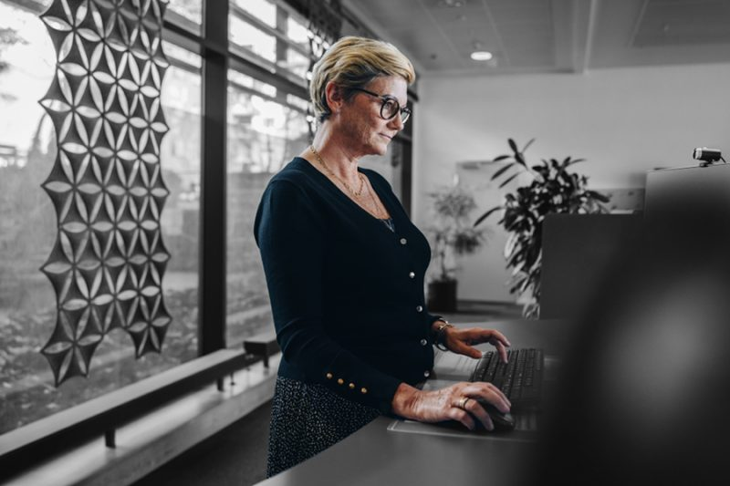 Senior businesswoman working at standing desk. Woman employee working on desktop computer at ergonomic standing desk.