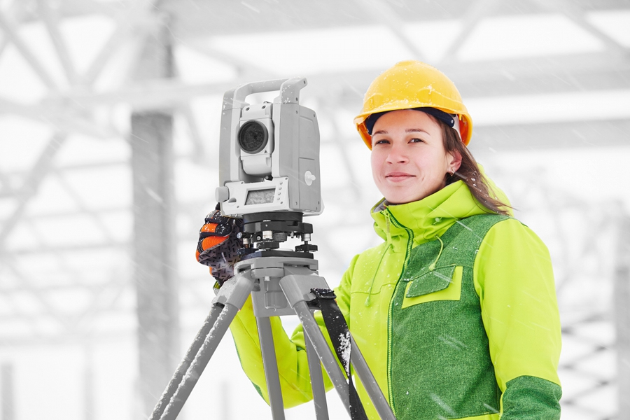 surveyor worker working with theodolite transit equipment at building construction site outdoors
