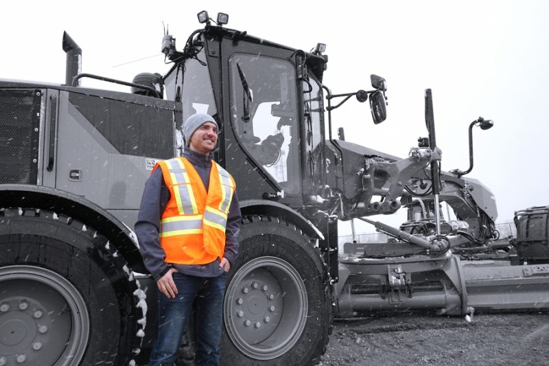 a man in safety gear stands in front of a grader