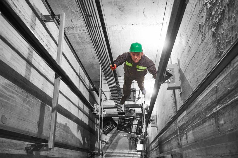 lift machinist worker adjusting elevator mechanism in elevator shaft hoistway