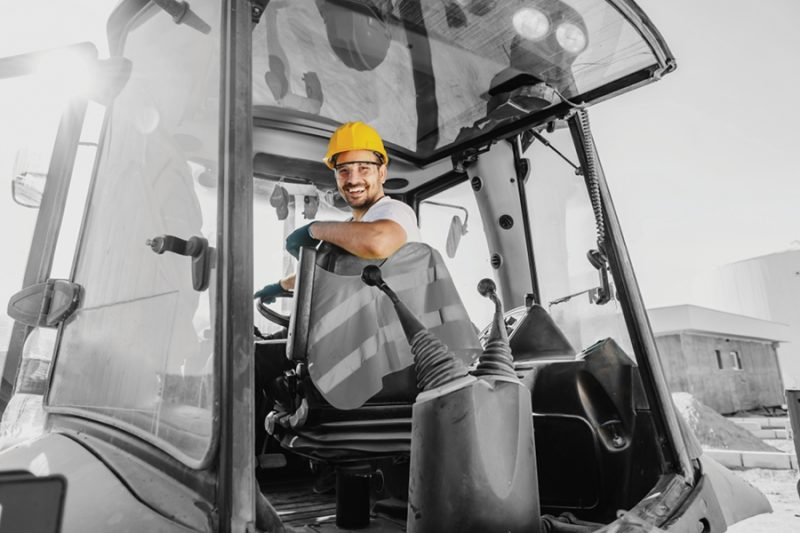 Smiling worker with helmet driving an excavator