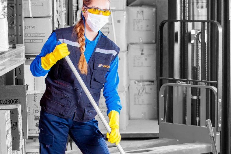worker using cleaning supplies and wearing PPE