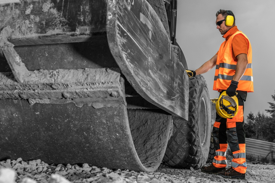 a man in safety gear stands next to a paving machine