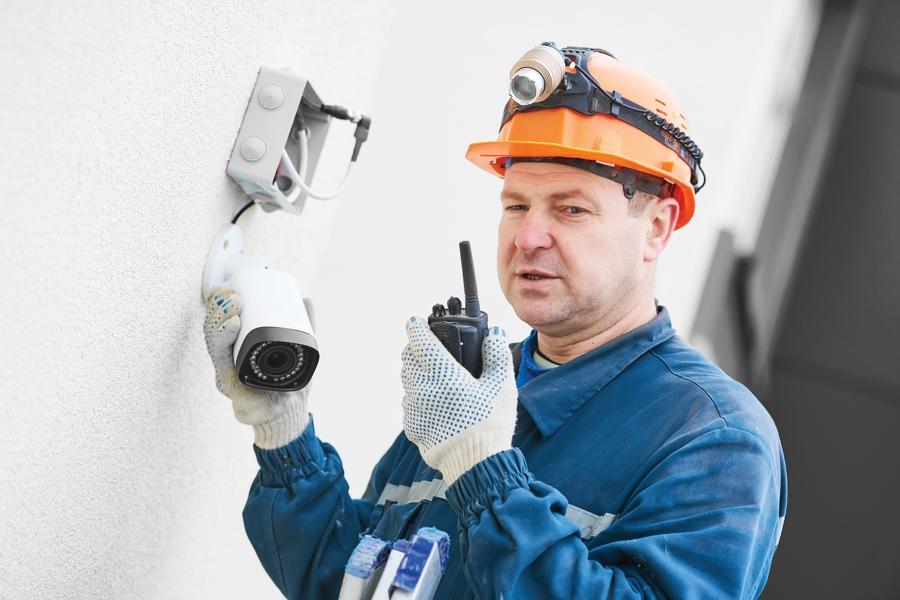 Technician adjusting wall surveillance camera