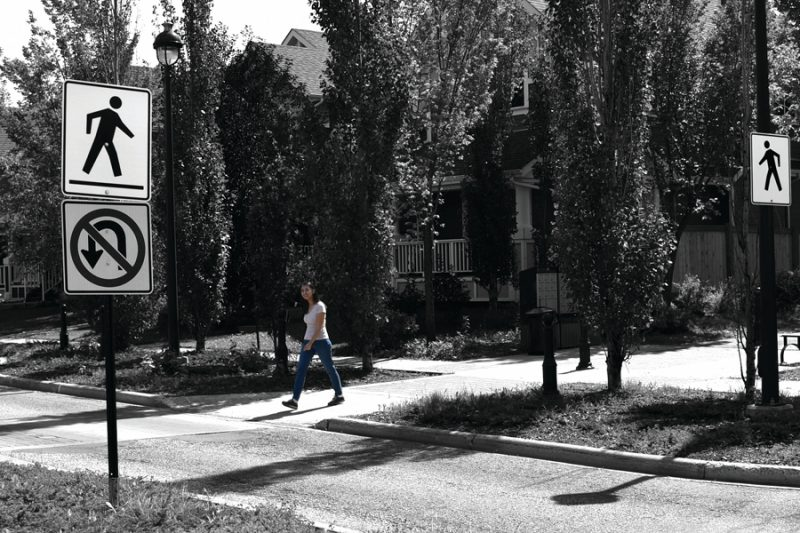 A woman crosses the street via a crosswalk marked by signs