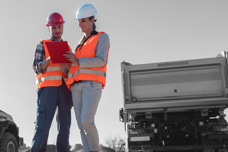 two workers discussing the contents of a clipboard near a truck hauling gravel