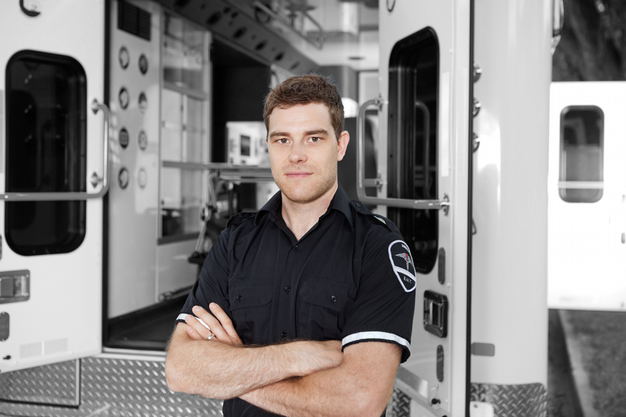 Paramedic in uniform standing in front of an open ambulance