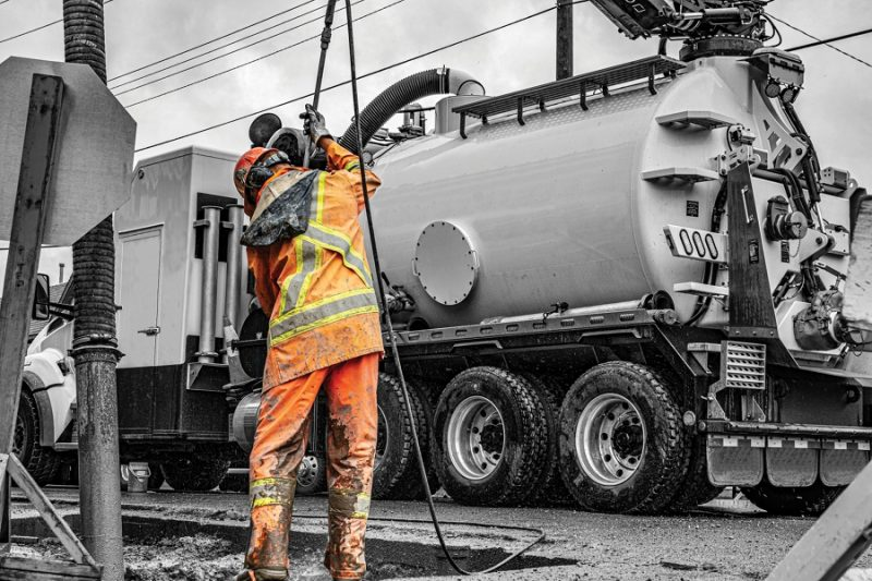 a worker in safety equipment stands next to a vacuum truck