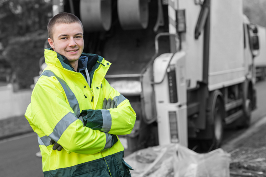 garbage collection worker standing near a garbage truck